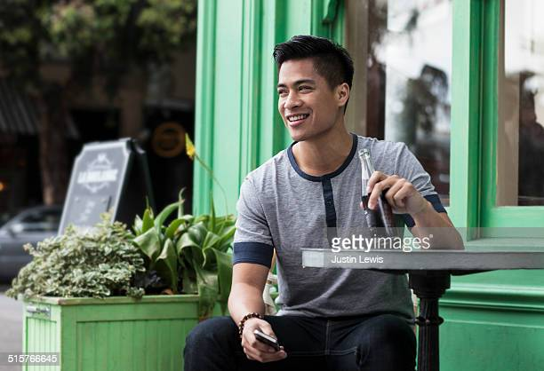 Young man at cafe with soda and phone smiling
