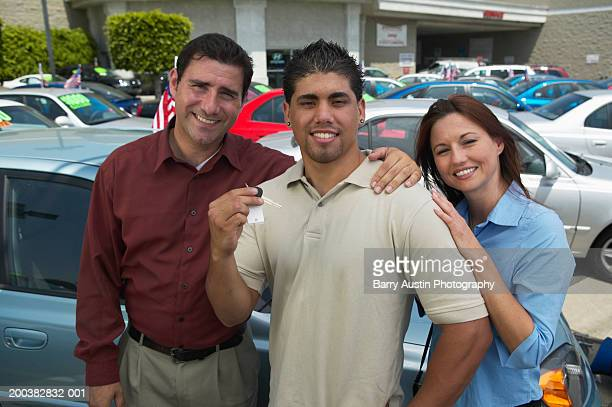 Young man at car lot with parents, holding keys, portrait