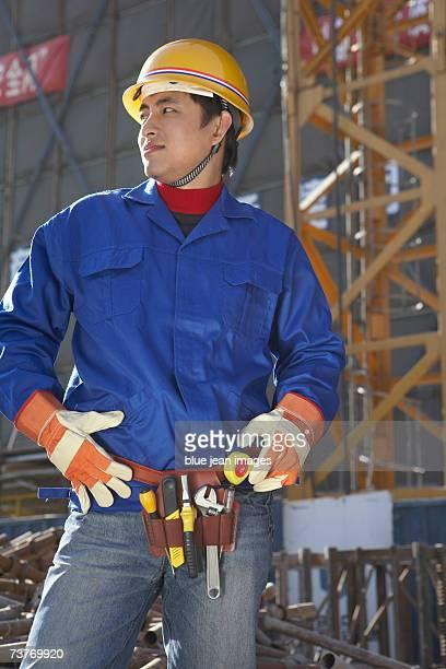 Young man at construction site, displaying tool belt, close up.