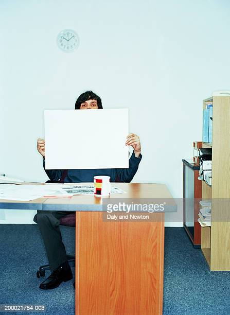 Young man at desk holding sheet of white card, portrait