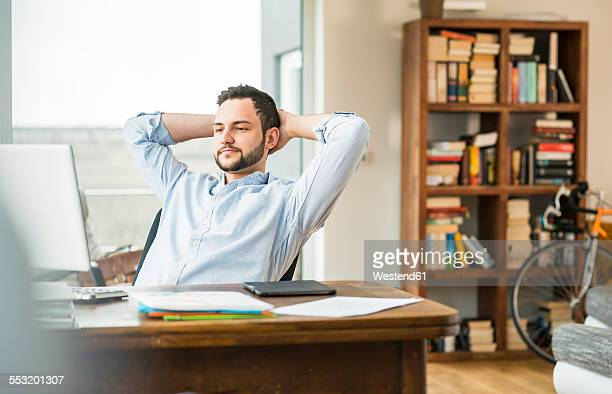 Young man at desk leaning back