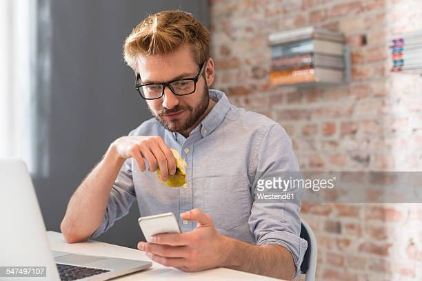 Young man at desk with cell phone and laptop