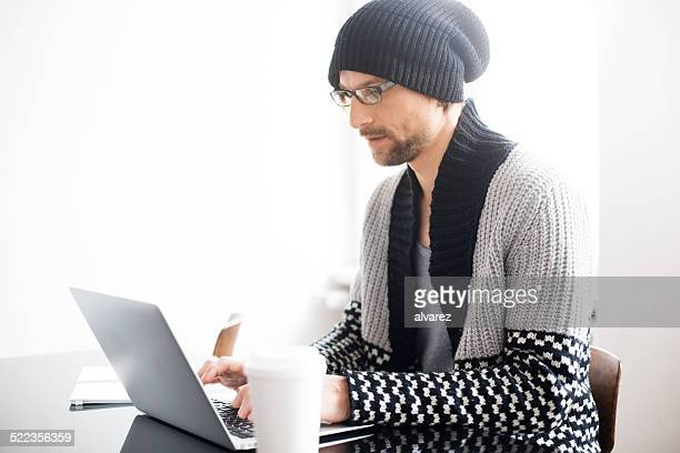 Young man at his desk working on laptop