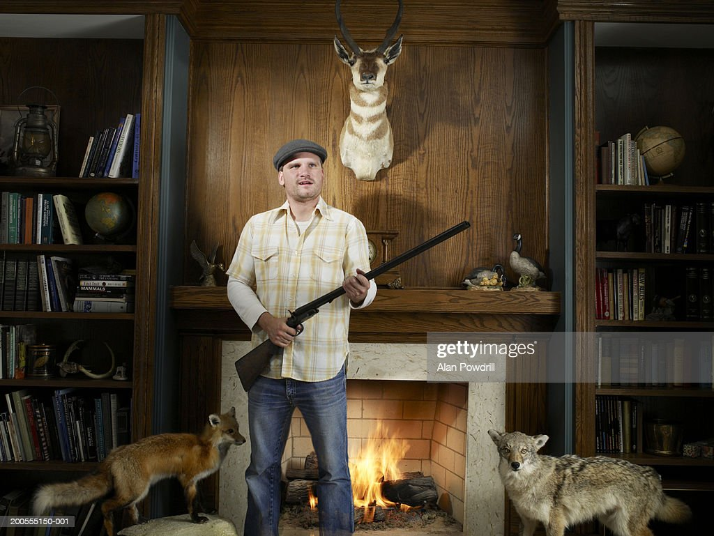 Young man at home between hunting trophies, holding rifle : Stock Photo