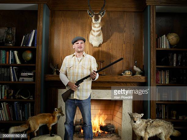 Young man at home between hunting trophies, holding rifle