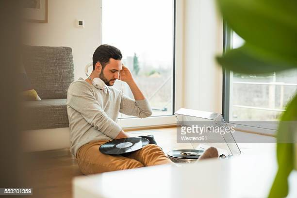 Young man at home listening to music from turntable