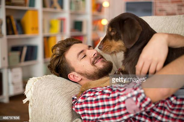 Junger Mann mit seinem Hund zu Hause fühlen.