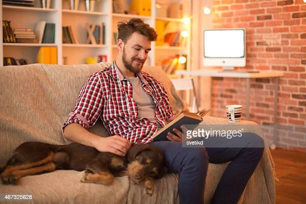 Jeune homme à la maison avec son chien.