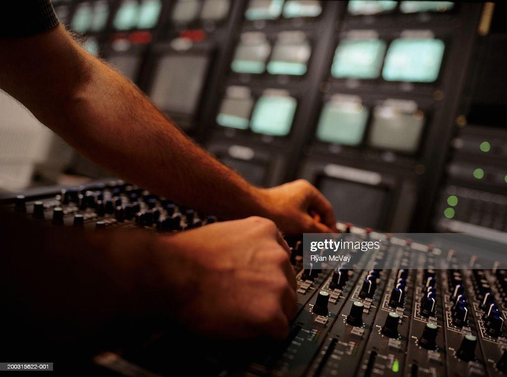 Young man at mixing console in television studio, close-up, surface view