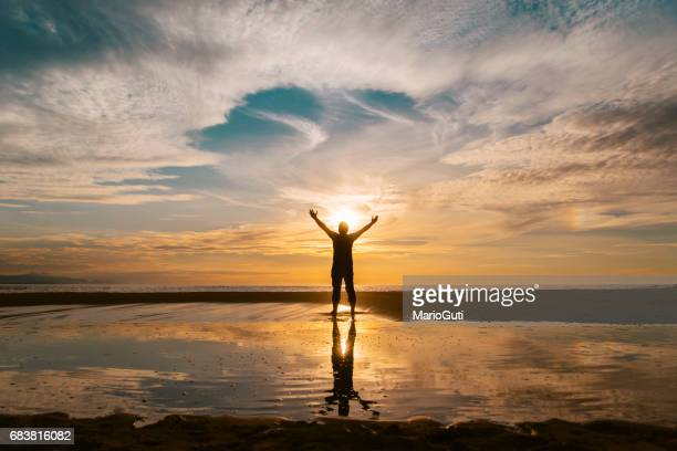 Young man at sunset and reflection