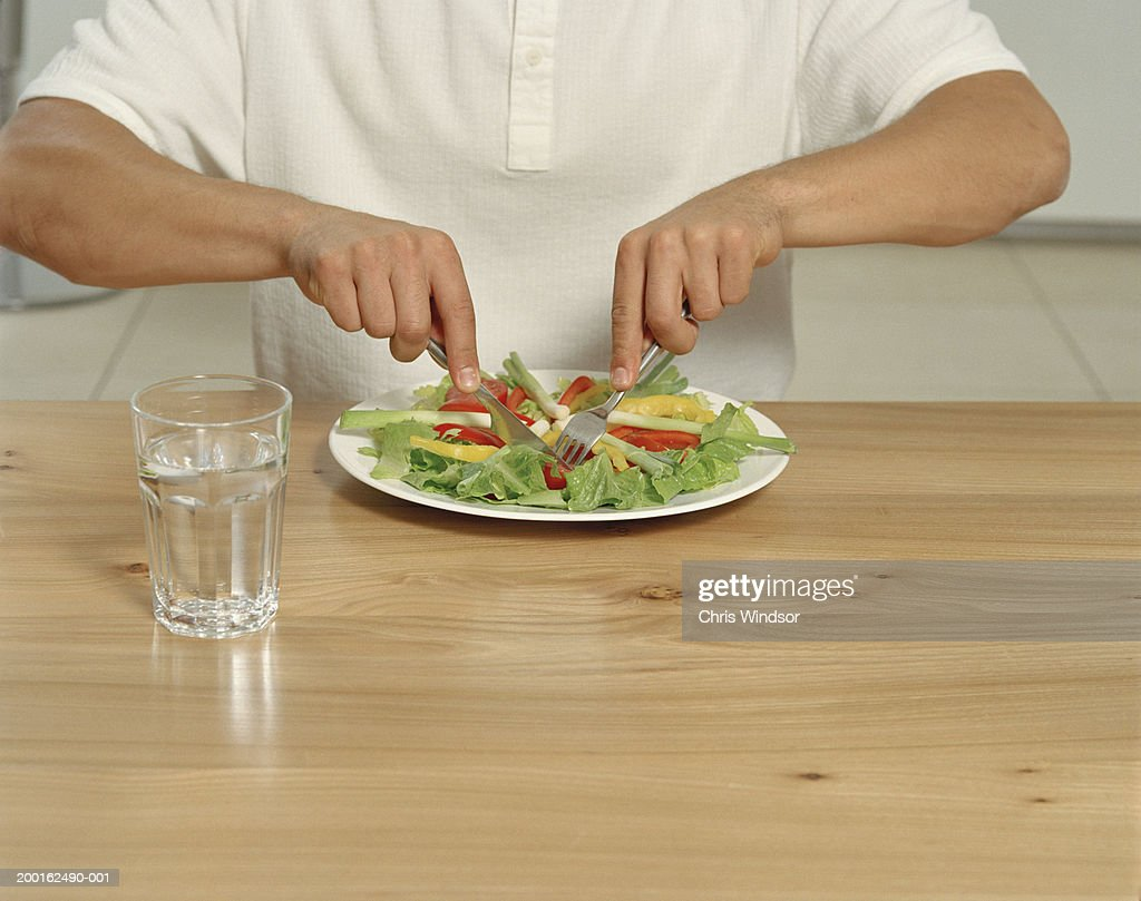 Young man at table eating salad, mid section : Stock Photo