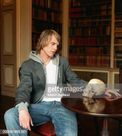 Young man at table staring at skull : Stock Photo