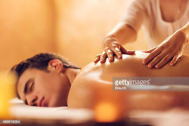 Young man at the spa receiving back massage.