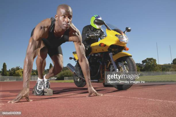 Young man at the starting position on a running track along side a motorcycle