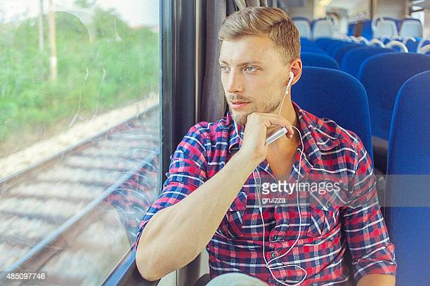Young man at train using mobile phone and earphones