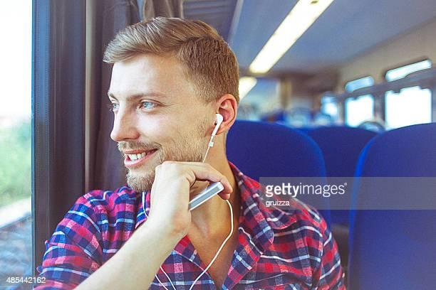 Junger Mann im Zug mit Handy und Kopfhörer