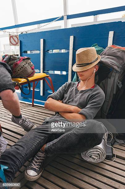 Young man backpacker relaxing on his luggabe