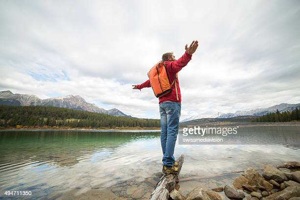 Young man balances on log above lake arms outstretched