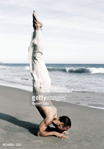 Young man balancing on arms on beach, profile : Stock Photo