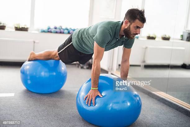 Junger Mann balancing auf zwei fitness Bälle in ein fitness-Center.