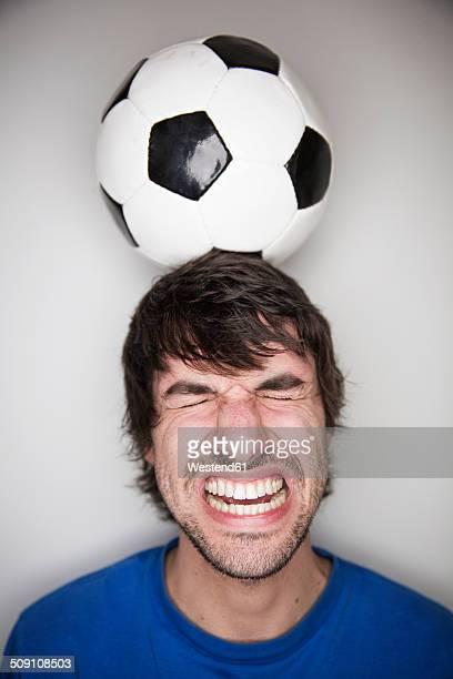 Young man balancing soccer ball on head