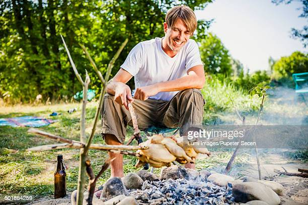 Young man barbecuing on the riverside, foothills of the Alps, Bavaria, Germany