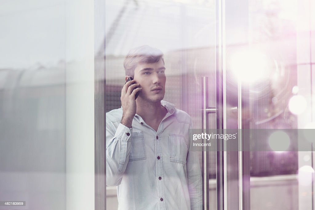 Young man behind illuminated reflective glass talking on smartphone : Stock Photo