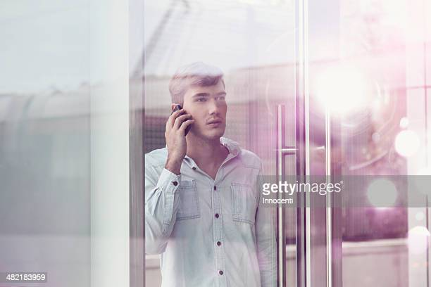 Young man behind illuminated reflective glass talking on smartphone