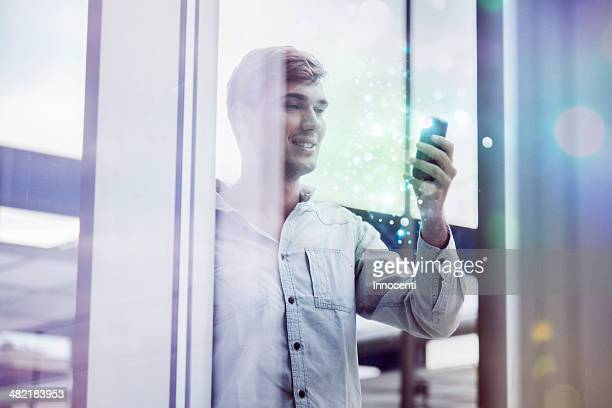 Young man behind reflective glass looking at illuminated smartphone