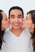 Young man being kissed by two young women