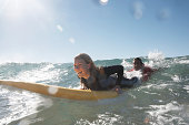 Young man being towed in sea by young woman on surfboard, smiling