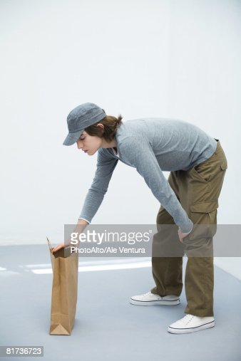 Young man bending over, looking in paper shopping bag, side view