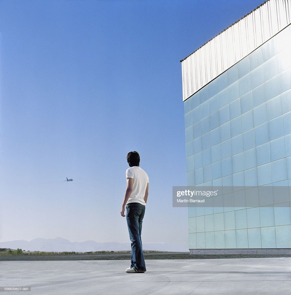 Young man beside reflective building, looking at plane, rear view : Stock Photo