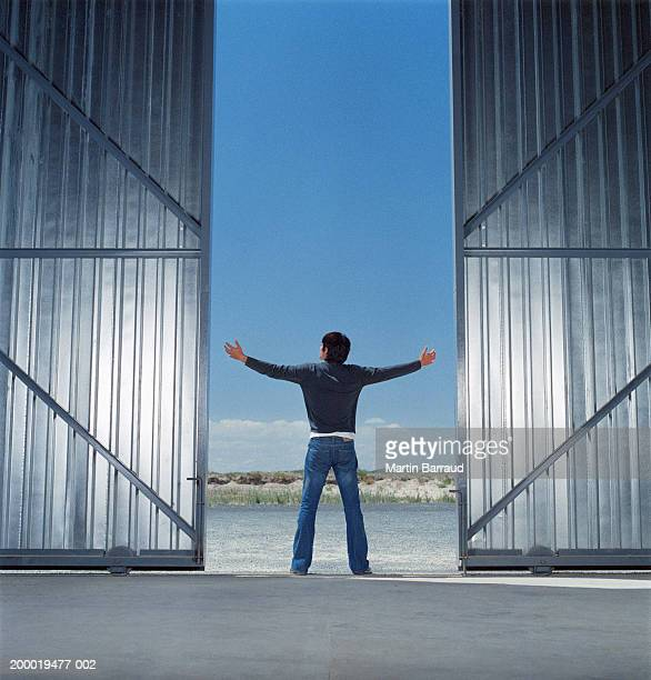 Young man between open warehouse doors, arms outstretched, rear view