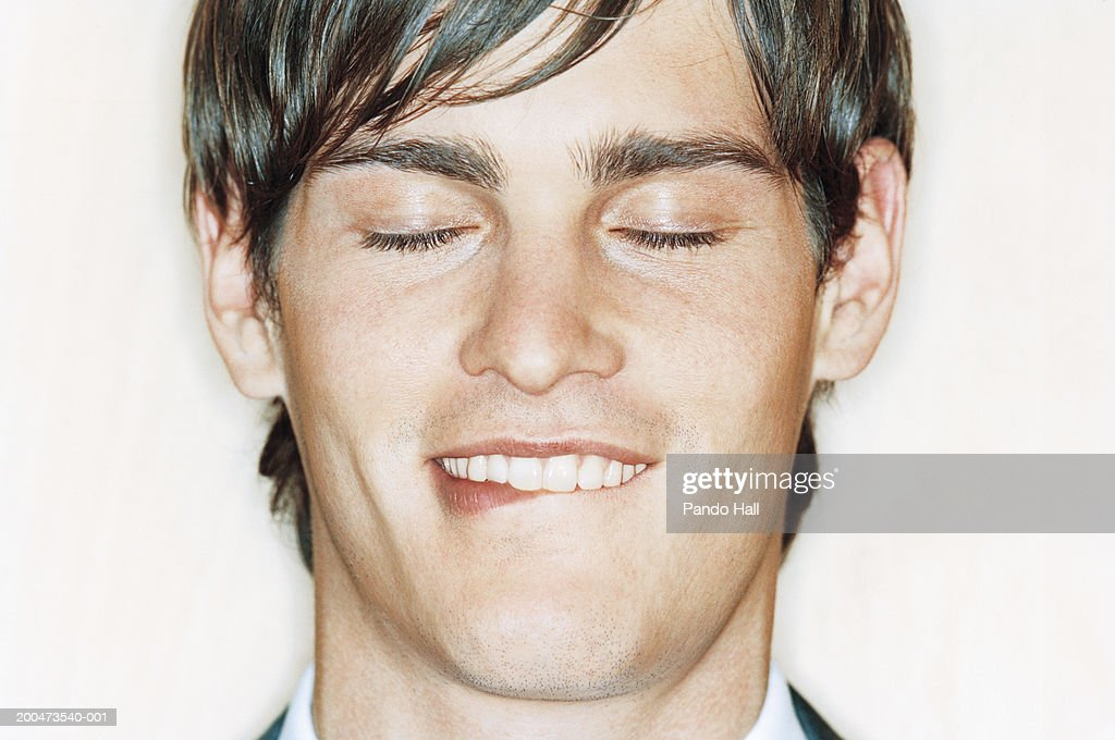 Young man biting lip, smiling, eyes closed, close-up