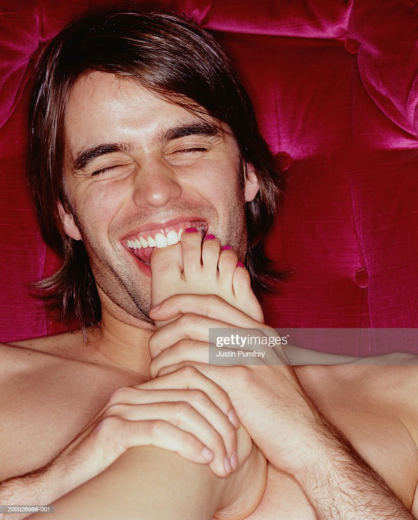 Young man biting woman's big toe, close-up : Stock Photo