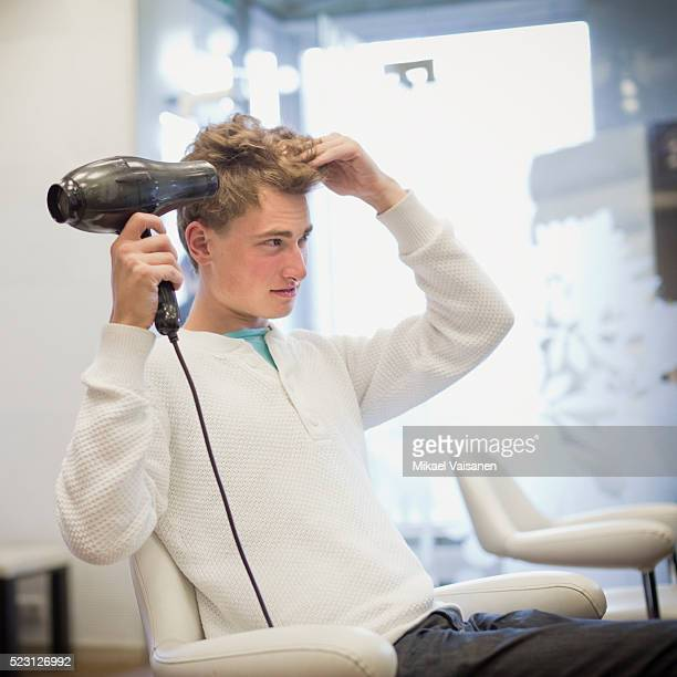 Young man blow drying his hair