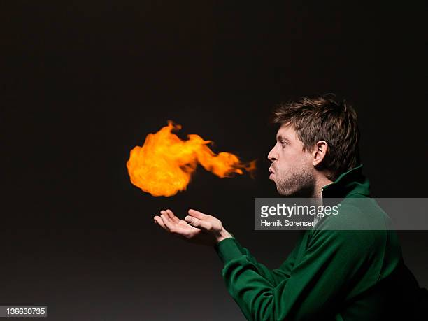 Young man blowing fireball