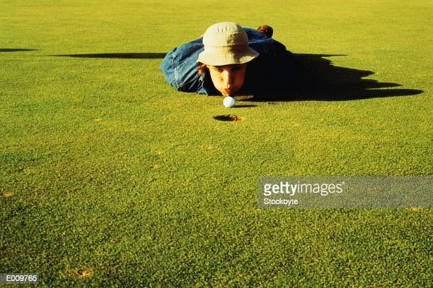 Young man blowing golf ball into hole