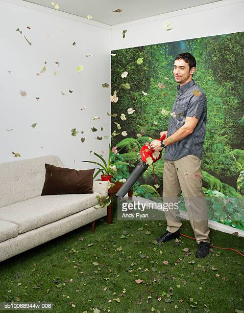 Young man blowing leaves in living room decorated with nature
