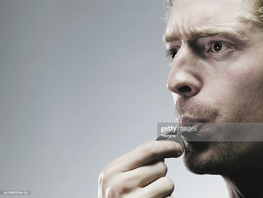 Young man blowing whistle, close-up : Stock Photo