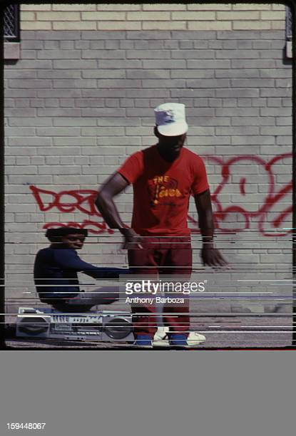A young man breakdances on a city street while his friend sits on a boombox behind him 1980s