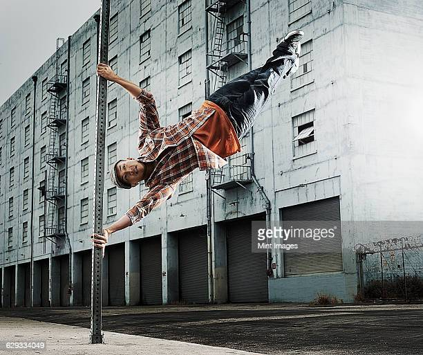 A young man breakdancing, leaping in the air, and stretching out.