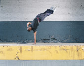 Young man breakdancing on loading dock, balancing on one hand
