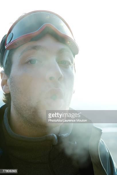 Young man breathing out into cold air