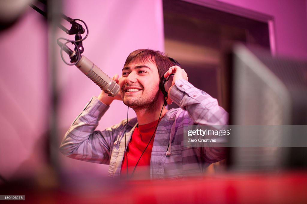 Young man broadcasting in recording studio, smiling