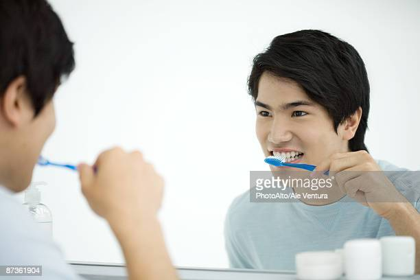 Young man brushing teeth, looking at self in mirror