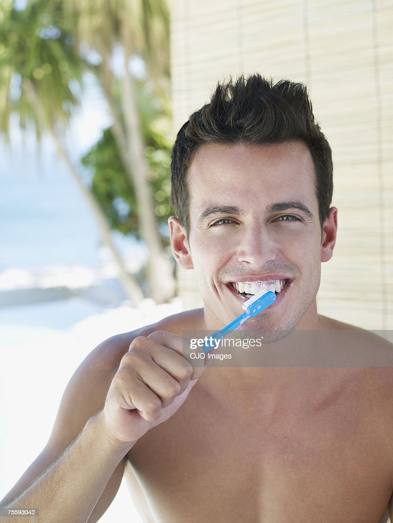 Young man brushing teeth : Stock Photo