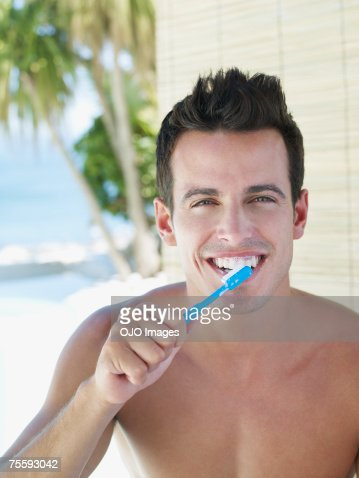 Young man brushing teeth : Stockfoto