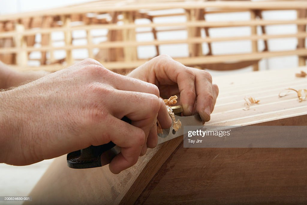 Young man building boat in workshop, close-up of hands : Stock Photo